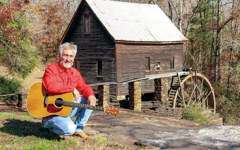 Musician Danny Thomas poses with his guitar in front of Ragsdale Grist Mill in Homer (Banks County).