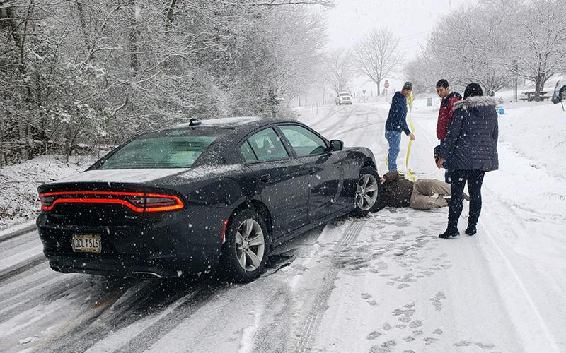 Motorists try to help each other during the icy conditions Saturday on Level Grove Road. Snow fell quickly around lunchtime while many drivers were out doing their weekend errands, causing many minor accidents.