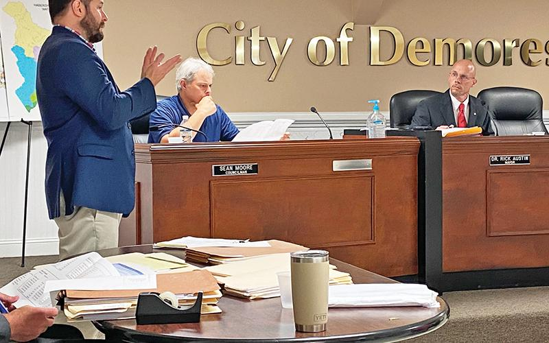 Cornelia Mayor John Borrow (left) makes a presentation Tuesday to the Demorest City Council, including Councilman Sean Moore (seated middle) and Mayor Rick Austin. Photo by ERIC PEREIRA