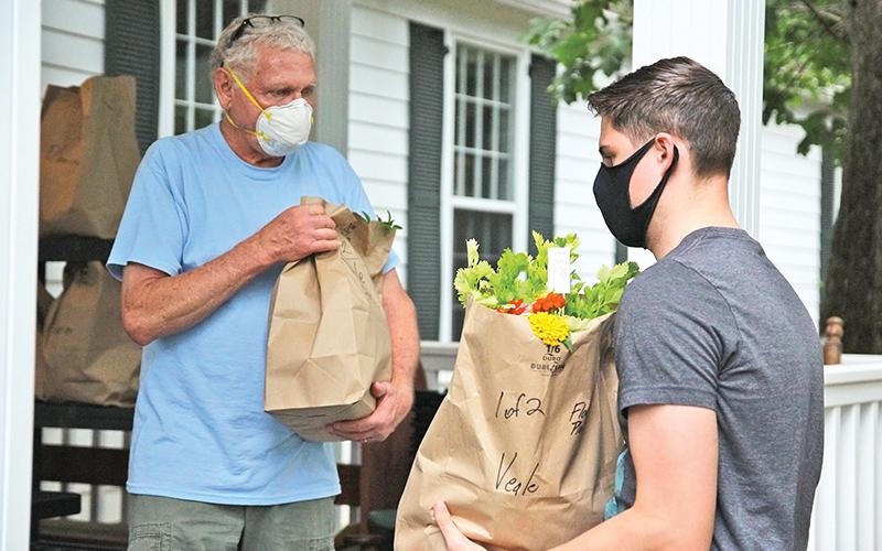 Carson Veale (right) from Clarkesville picks up his Northeast Georgian  Locally Grown produce with the assistance of volunteer Tom Gagnon. Locally grown foods have seen a surge during the pandemic crisis.