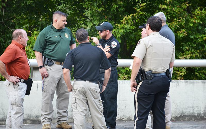 Officers discuss the body found in Clarkesville on Thursday afternoon.