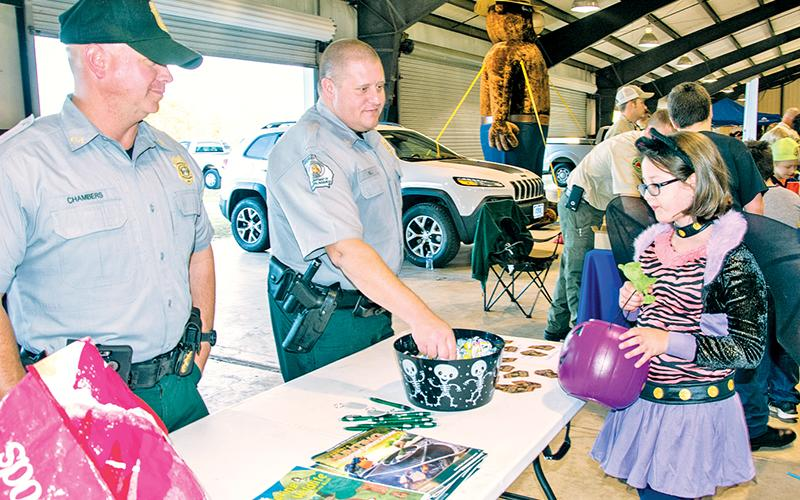 Georgia Department of Natural Resources officers Chad Chambers (left) and Joe Hill offer candy to a cool cat at last year's E-911 Halloween event in Habersham County. The event has been cancelled for this year due to lingering COVID-19 concerns.