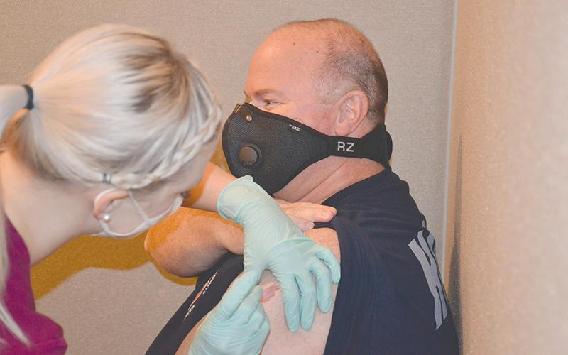 Habersham Emergency Services paramedic Greg Ramey gets his COVID-19 vaccine Wednesday from nurse Lauren Martin at Habersham Medical Center.