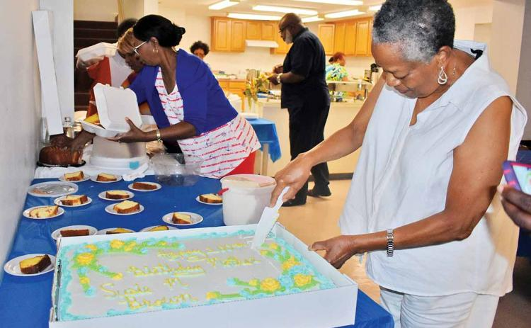 Gwen Brown, daughter of Susie Brown, cuts the cake at Susie Brown's 100th birthday party earlier this month at a Clarkesville church. (Photo/CHAMIAN CRUZ)