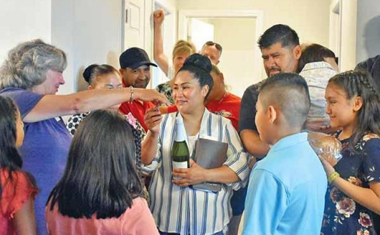 Shown is Habitat for Humanity of Northeast Georgia Executive Director Nanette Baughman reaching over to hug Deyci Rodriguez, surrounded by the rest of the Rodriguez family, who on Sunday were dedicated Habitat's 71st house. (CHAMIAN CRUZ/Staff)