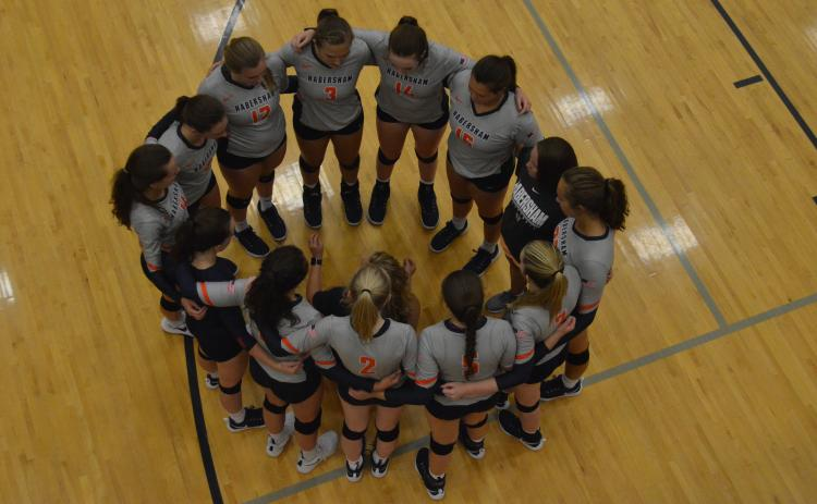 The HCHS Volleyball team huddles during a timeout Thursday.