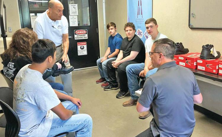 Habersham Central High School students in the dual-degree welding program at North Georgia Technical College were fitted Thursday morning for their safety boots. Students shown sitting in a circle, left to right, are 10th-grader Gabe Blackburn, 12th-grader Katie McCoy, 11th-grader Joshua Brock, 11th-grader Adrian Frankum and 10th-grader Drew Maneg. (Photo/CHAMIAN CRUZ)