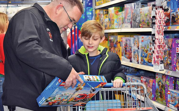 Cornelia Fire Marshal Lt. Josh Hazle approvingly looks at 10-year-old Colton Abbott's pick of Lego's. The two were among 14 other children and several firefighters and police officers with the city of Baldwin who participated in the annual Shop With a Hero.