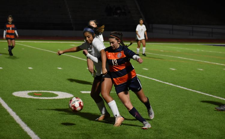 Habersham Central's Addie Penick fights for the ball with a Lanier High School defender Wednesday.
