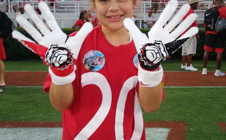 Michaela Krippner, 11, of Mt. Airy, holds up a pair of game-worn gloves gifted to her by University of Georgia safety J.R. Reed.