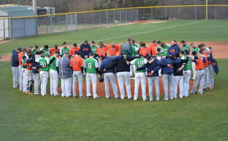 Members of the Habersham Central and Franklin County high school baseball teams pray for Raider Hadden Carswell before their game Friday. Carswell was seriously injured in an automobile accident Feb. 24.
