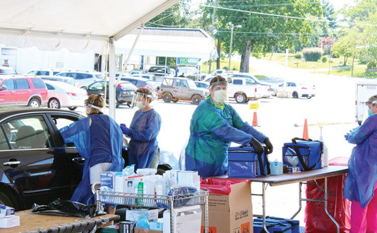 Healthcare workers test patients at a drive-thru COVID-19 event on June 13 in Cornelia. Photo by ISAIAH SMITH/staff