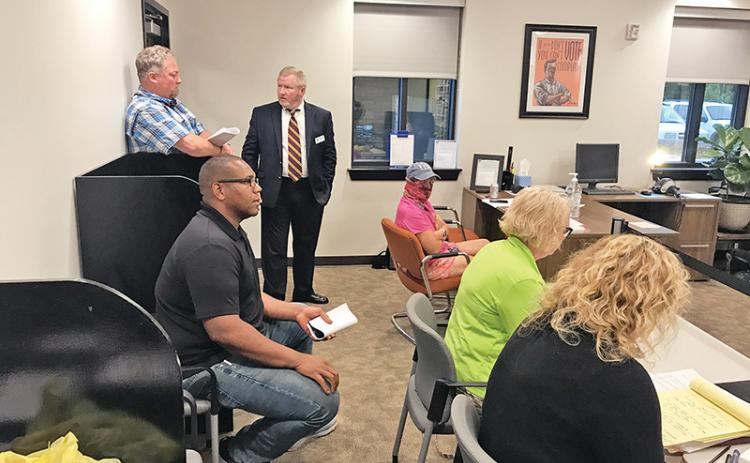 Trent Davis (seated left) listens to the Board of Elections' announcement of the recount results Monday night.