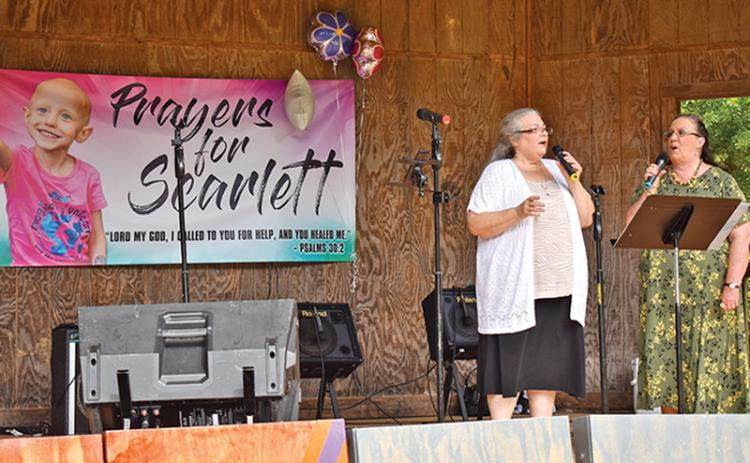 Renee Johnson and Connie Perry sing during the benefit for Scarlett LaCount at Pitts Park on Saturday.