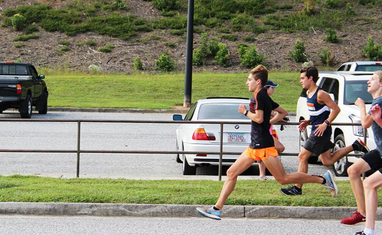 Andrew Kivett (running in front) leads Habersham Central's cross country team in several different ways this season.