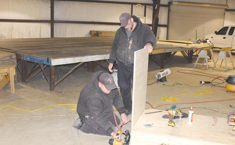 Habersham County Sheriff's Deputy Jason Eller (left) uses a nail gun to construct a judge's bench while deputy Paul Jardine (right) holds the wood in place. The pair also constructed a witness stand to be used for superior court in the aquatic center.