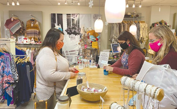 Sarah Mobley purchases a pair of earrings from Erin London Store in Clarkesville on Small Business Saturday as Meg Luke (left behind counter) and Jeanie Huddleston help out.