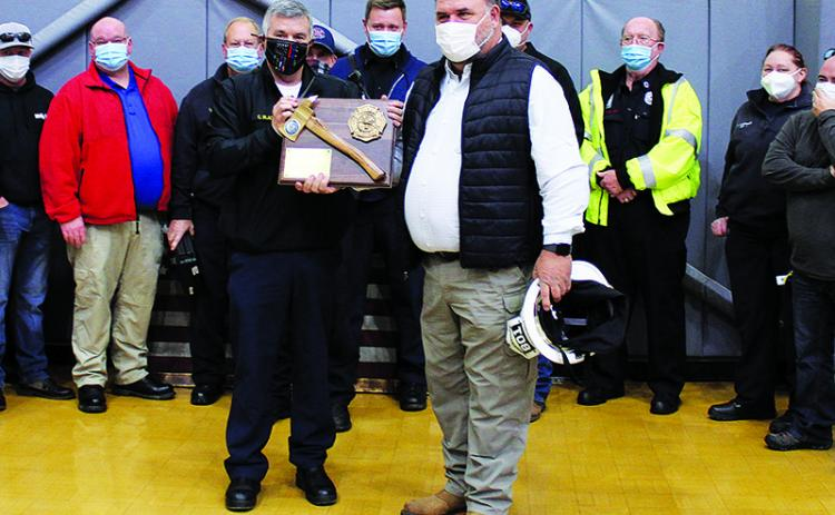 Habersham County EMS Director Chad Black (left) presents Jeff Cain (right) with a plaque commemorating his years of service while surrounded by the County's EMS workers. Black also thanked Cain for his work in helping merge the county's firefighters and EMS into a single department like it is today.